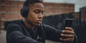 Boy Listening on phone and headphones